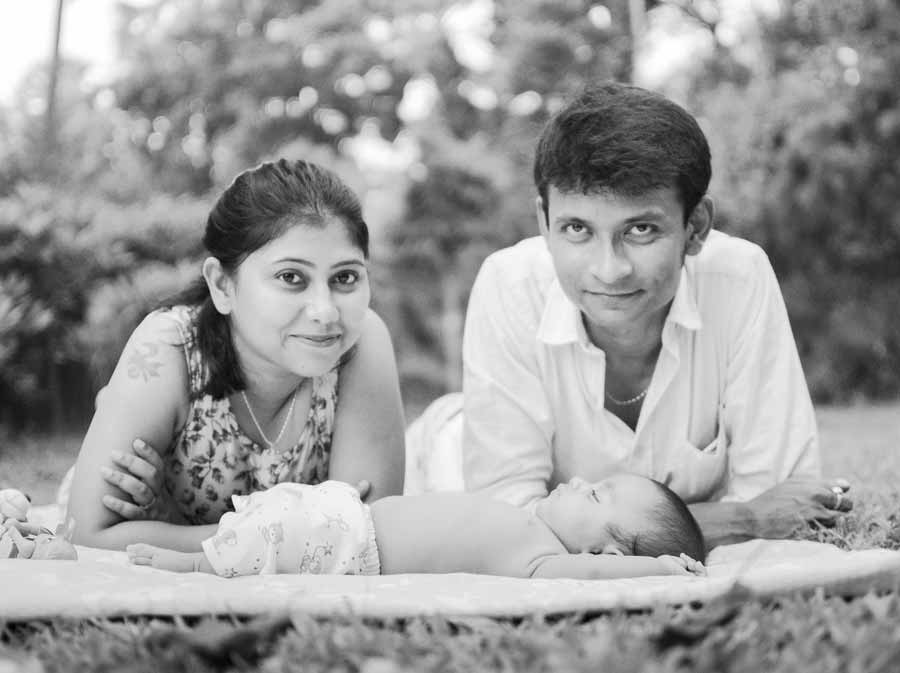 black & white outdoor photoshoot of newborn baby with family