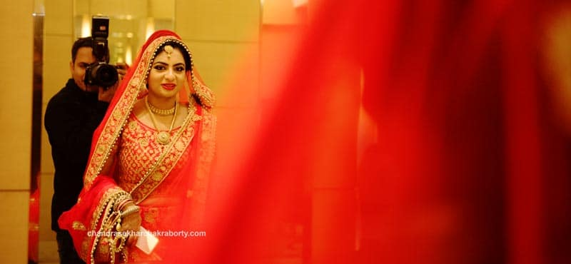 Indian wedding photographer Chandrasekhar, taking pictures of the bride reflection standing in front of the mirror