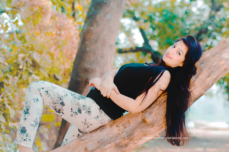 a beautiful girl lying on the tree, using orange and teal effect in outdoor photoshoot, Nikon 50mm 1.8 D