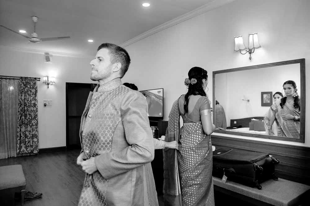 Bride & groom getting ready to wear indian dress before reception ceremony. photojournalism style Black & White image