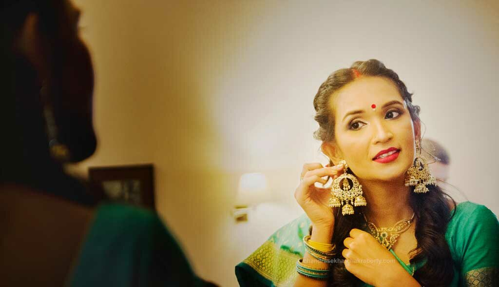 indian bride earrings later in front of the mirror